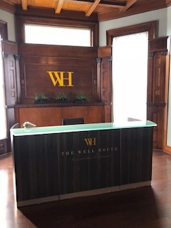 The Well House Spa for Beauty and Wellness Treatments - Reception Desk with Sign 3 1 - A collection of Spa, beauty, and other wellness treatments inspired to help you lead a happier, healthier life.